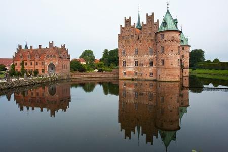 Egeskov castle slot landmark fairy tale castle in Funen Denmark view from the lake photo