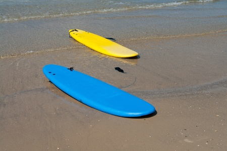 Colorfull surf boards on a  sandy beach ready for extreme action sport photo