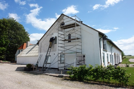 exterior house: Man on scaffolds painting a house during exterior renovations