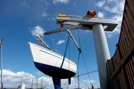 Sailboat lift up by a heavy industrial boat lifter for maintenance photo