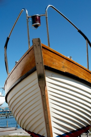 Details of the front part of a prow of a wooden yacht boat  with clear blue sky background