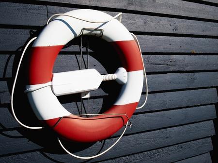 life buoy: Life buoy preserver ring belt hanged on a dark wooden wall       Stock Photo