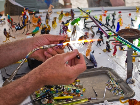 Glass blower craft artist at work forming small figurines