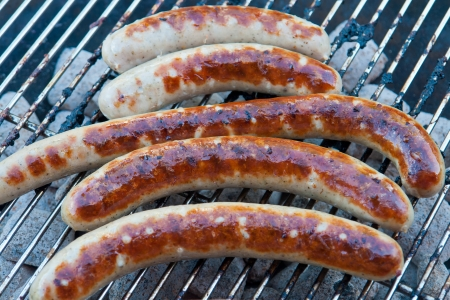 Grilled traditional German sausage hot dog on charcoal wurst BBQ grill