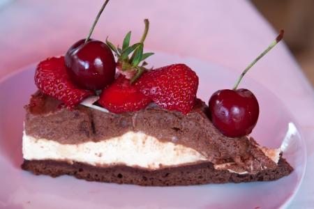 Delicious glazed chocolate cake decorated with cherries and strawberries photo