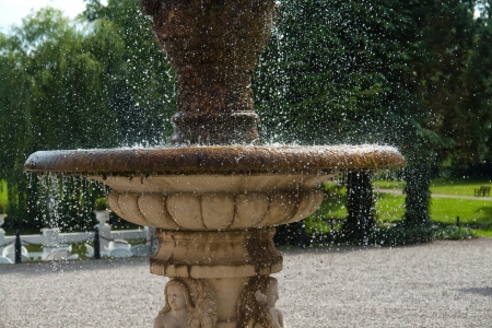 The gush of clear water splashes in a tradional European ornated stone fountain photo