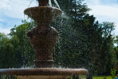 gush: The gush of clear water splashes in a tradional European ornated stone fountain