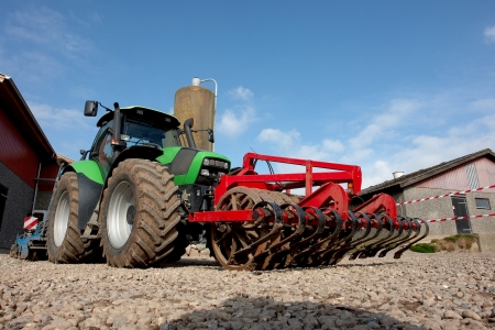 plows:  Modern tractor with a plow in a farm agriculture background image                               Stock Photo