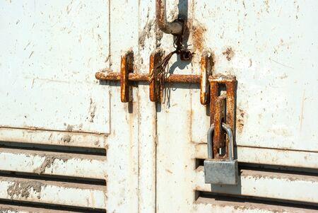 keep gate closed: Metal door locked with an old rusty lock