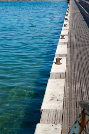 bollards: Mooring bollards in a port harbour with clear sea water - marine background image