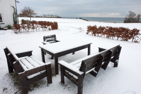 Garden furniture in winter time with snow covered landscape