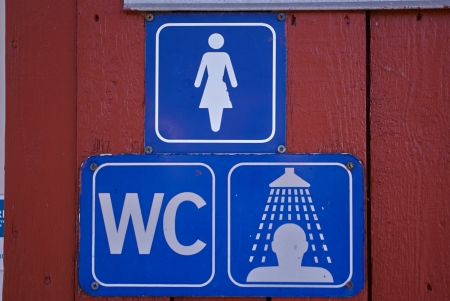Blue sign of public toilets WC shower for women on a wooden wall photo