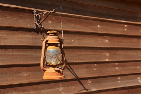 oil lamp:  Classical rusty oil lamp hanged on a wooden wall                               Stock Photo