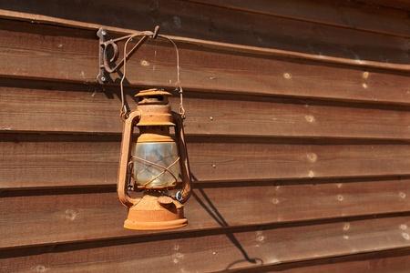 candil: Lámpara de aceite oxidado clásico colgado en una pared de madera