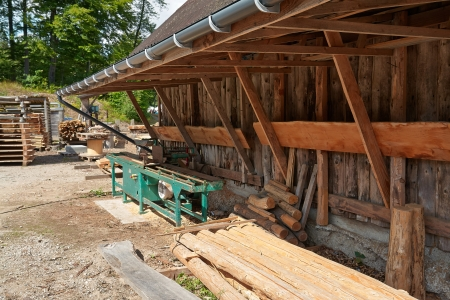 lumber mill:  Small traditional sawmill lumber mill with a saw table and wood logs