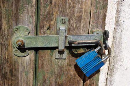 Wooden door locked with a heavy metal lock padlock photo