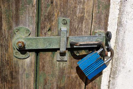 keep gate closed: Wooden door locked with a heavy metal lock padlock Stock Photo
