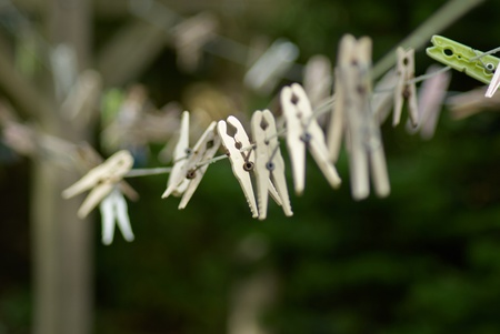 Plastic laundry clothespins clamps on rope shallow depth of field view photo