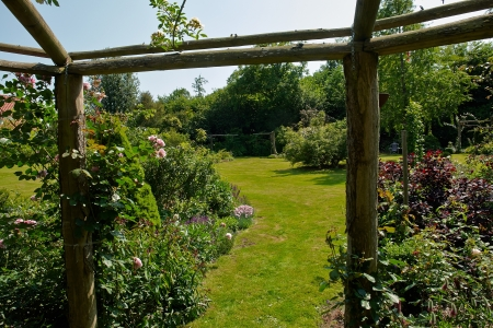 Wooden pergola gazebo in a beautiful blooming garden full of flowers and green plants Stock Photo