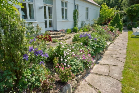 Beautiful delightful flower beds in front of a house English garden