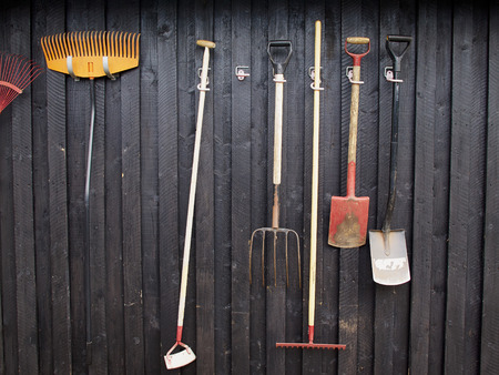 Gardening tools hanged on a black painted wooden wall Standard-Bild