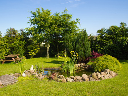 arden: Beautiful classical garden fish pond surrounded by grass gardening