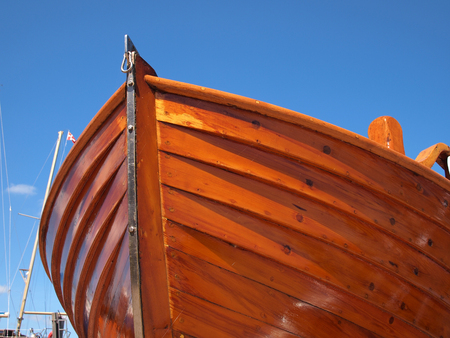 Prow of a small wooden boat with clear blue sky background