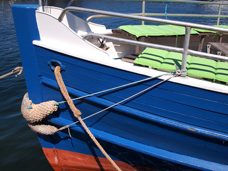 prow: Prow of a small wooden tour boat docking in a marina