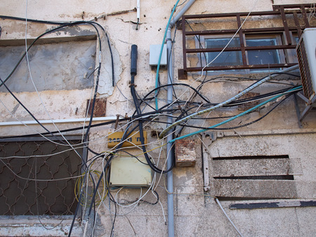 disorganization: Tangled electric cable mess on a wall of building