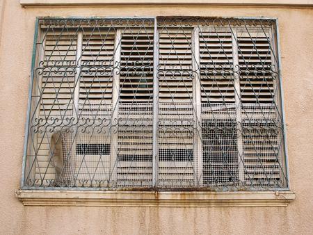 rejas de hierro: Ventana sucio con barras de hierro oxidado en una zona del centro urbano