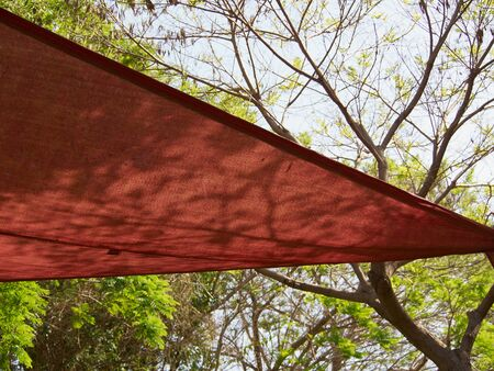 shade: Colorful shade net shaped like a triangle in a park Stock Photo