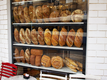 window reflection: Assortment of baked bread in a bakery window display