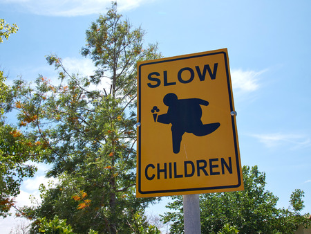 children play: Slow Children at Play street sign with blue sky background Stock Photo