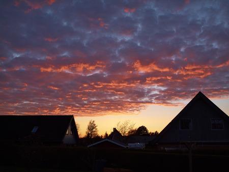 cielo atardecer: Naranja ardiente cielo espectacular puesta de sol entre las casas