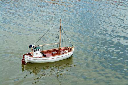 small boat: Sailing remote control model scale sail boat in a small lake
