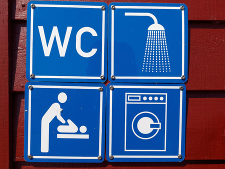 baby changing sign: Blue sign of public toilets WC shower washing machines baby changing in a camping site Stock Photo