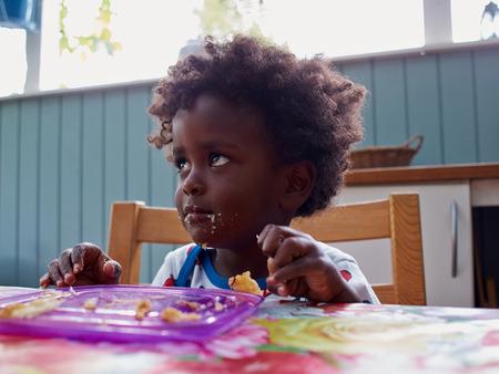 Schattige zwarte Afrikaanse baby eten met voedsel volledig gezicht