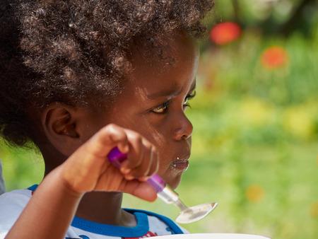 Entzückende schwarze African Baby Ernährung mit Lebensmitteln vollem Gesichts Standard-Bild - 40902233