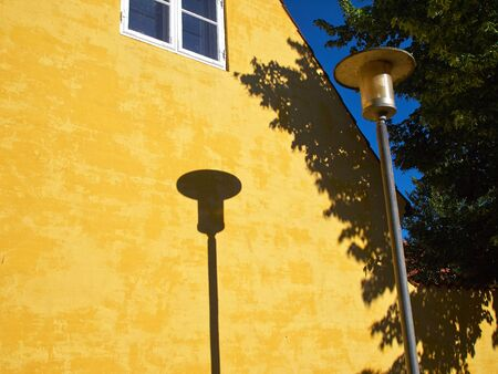 street lamp: Lamp Post Street Road Light Pole casting a shadow over a yellow house