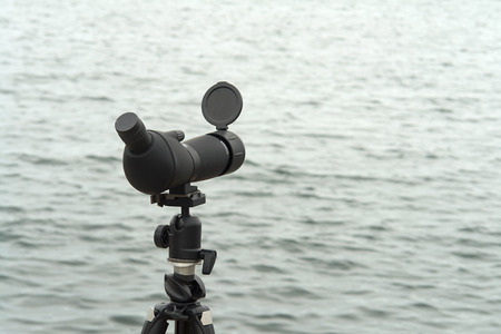 monocular: Nature birdwatching spotting scope monocular on a tripod near the water great outdoors activity Stock Photo