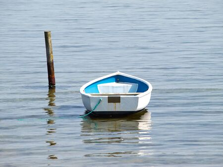 dingy: Moored small dingy rowing boat on still calm water