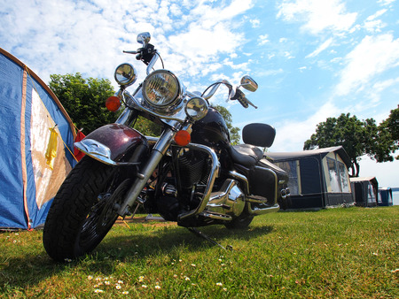 Big classical touring motorcycle motorbike in a camping site by a tent