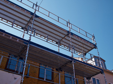 scaffolds: Modern sophisticated scaffolds on a house building under extensive renovations
