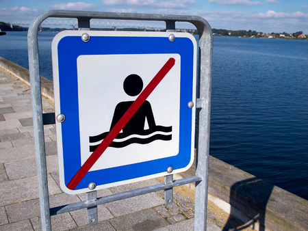 no swimming: No swimming danger warning sign by the beach ocean Stock Photo