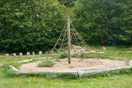 jungle gym: Jungle gym exercise equipment made of wood and ropes in a playground