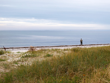 ocean fishing: Single fisherman angler standing with a fishing rod by the sea ocean
