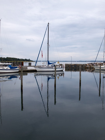 recreational: Recreational Sail Yacht in a small marina with reflection in the water