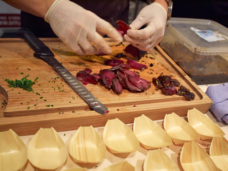 catering food: Bison Tenderloin cut into seving slices by a professional chef