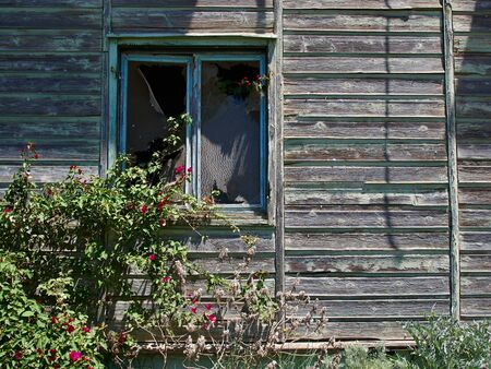 broken house: Details of an old weathered abandoned western colonial style wooden house shed Stock Photo