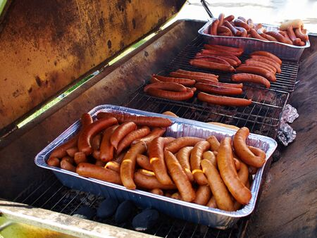 sizzle: Grilling selection of sausages on a cast iron BBQ barbecue grill
